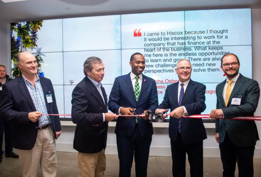 Leadership team cutting ribbon to Bermuda office